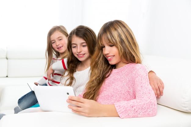 Drei kinderschwesterfreundmädchen, die zusammen mit tabletten-pc spielen