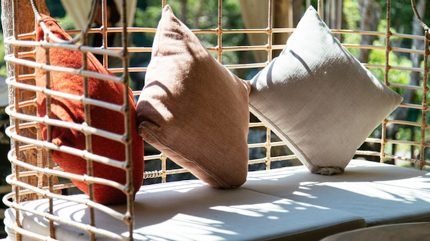 Drei kissen platziert auf einen stuhl mit sonnenschein, interieur