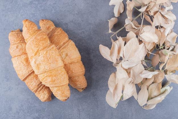 Drei klassische französische croissants mit dekorativen blättern über grauem hintergrund.