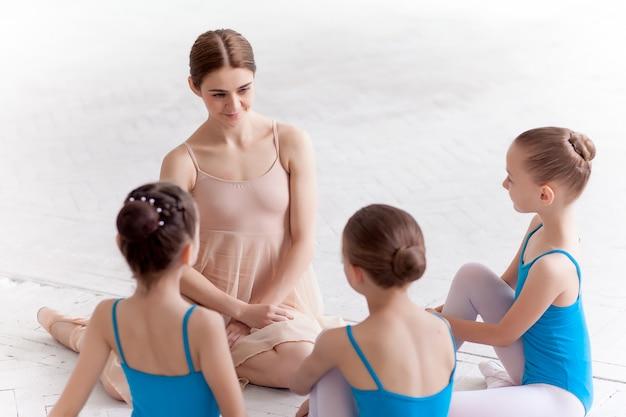 Drei kleine ballerinas tanzen mit persönlichem ballettlehrer im tanzstudio