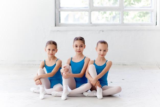 Drei kleine ballettmädchen sitzen und posieren zusammen