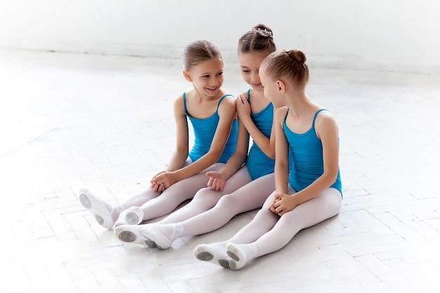 Drei kleine ballettmädchen sitzen und reden zusammen