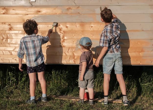 Drei kleine jungen streichen gemeinsam die wand eines holzhauses draußen. drei brüder helfen beim malen eines neuen hauses