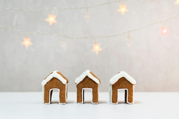 Drei kleine lebkuchenhäuser für teetasse und girlande auf hintergrund. weihnachtsbacken.
