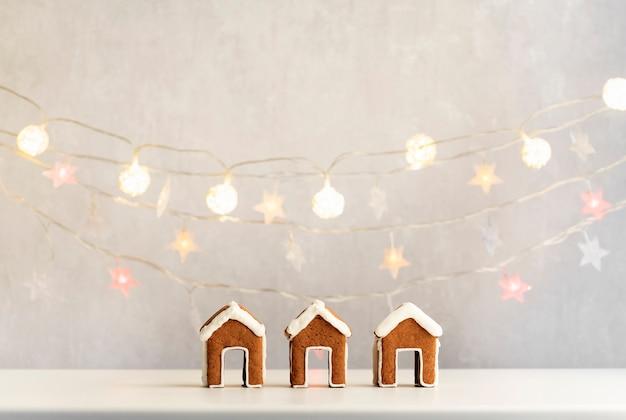 Drei kleine lebkuchenhäuser und weihnachtslichter auf hintergrund. weihnachtsbacken.