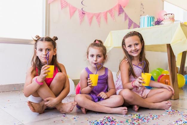Drei kleine mädchen, die saft trinken, wenn sie geburtstagsfeier zu hause feiern