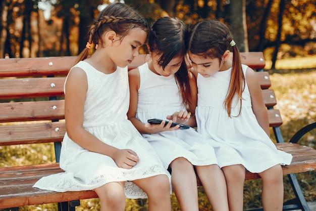 Drei kleine schwestern, die in einem sommerpark sitzen