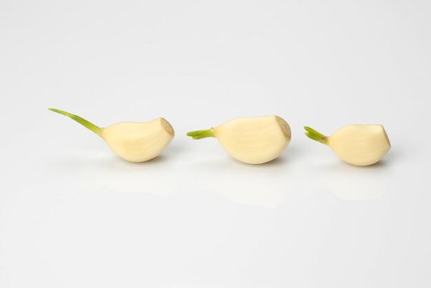 Drei knoblauchzehen auf einem weißen tisch