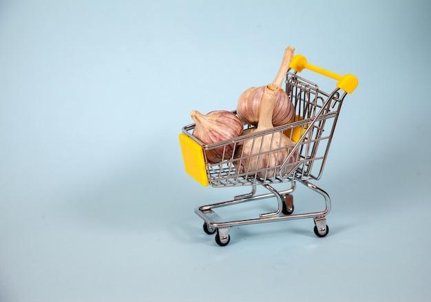 Drei knoblauchzehen liegen in einem supermarktkorb