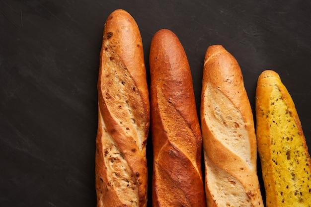 Drei knusprige französische baguettes liegen dunkelschwarze sesamkörner mit tischhintergrund