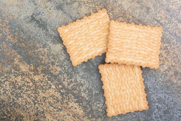 Drei köstliche kekse auf marmorhintergrund. hochwertiges foto