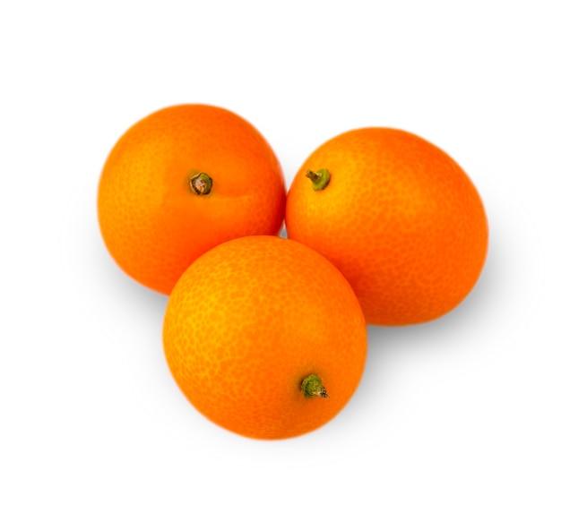 Drei köstliche kumquat, geschnitzt auf weißem hintergrund.