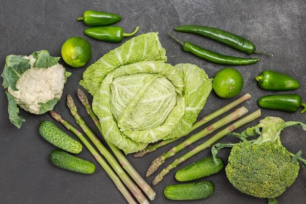 Drei kohlsorten. gurken, paprika und limetten, grüne paprika auf dem tisch. schwarzer hintergrund. flach legen