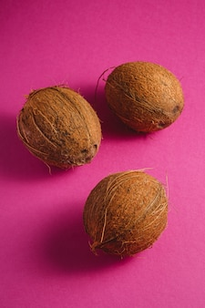 Drei kokosnussfrüchte auf lebendigem rosa lila einfachem hintergrund, tropisches konzept, winkelansicht