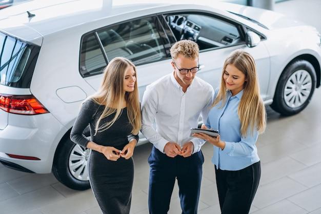Drei kollegen, die an einem autosalon arbeiten