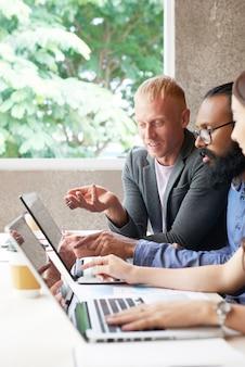 Drei kollegen, die an laptop im büro arbeiten und etwas besprechen