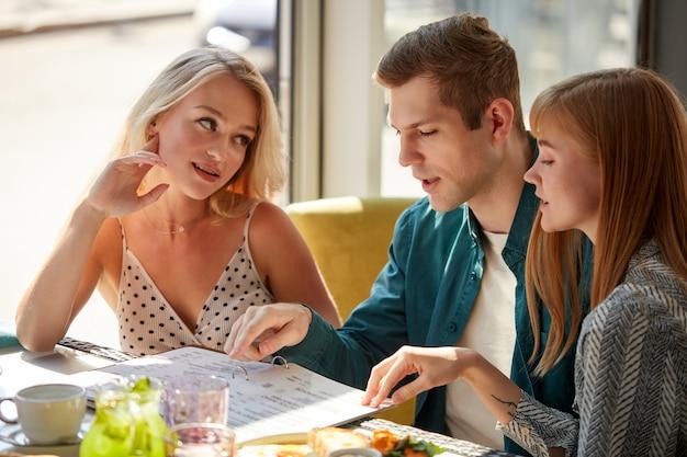 Drei kollegen im café besprechen das essen in der speisekarte