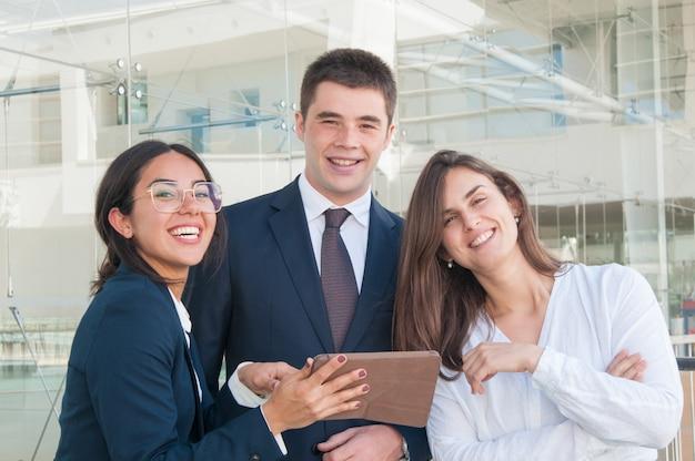Drei kollegen im korridor, die kamera betrachtend und lächeln