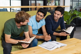 Drei Kommilitonen, die zusammen sprechen und studieren