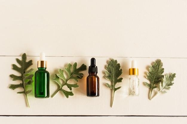 Drei kosmetikfläschchen mit einer pipette aus farbigem glas mit einem serum mit straffender wirkung. das konzept der naturkosmetik. ansicht von oben.