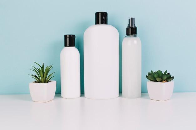 Drei kosmetikflaschen in der nähe von pflanzen