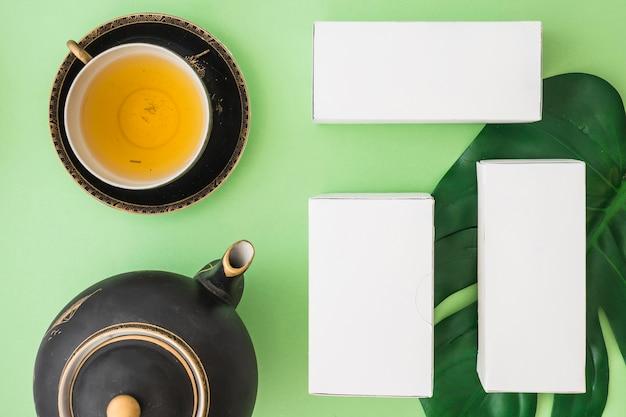 Drei kräuterkästen mit teeschale auf farbigem hintergrund
