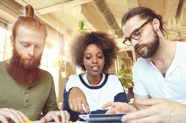 Drei kreative leute, die im café diskutieren: afrikanische frau, die ihre vision erklärt, auf den bildschirm des touchpads zeigt, bärtiger mann in brille, der aufmerksam zuhört, und rothaariger partner, der notizen macht