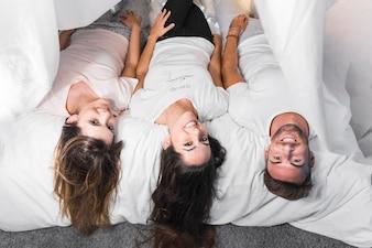 Drei lächelnde Freunde, die auf Bett liegen
