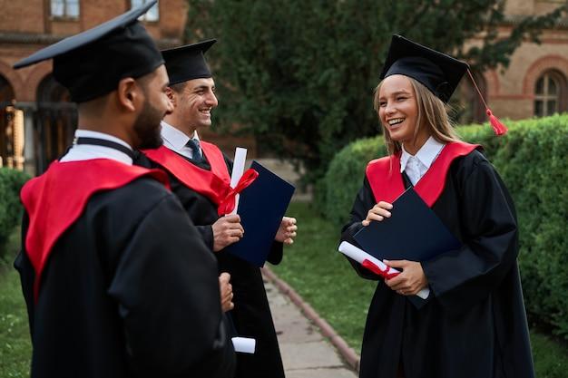 Drei lächelnde absolventenfreunde in abschlussroben, die auf dem campus mit diplom sprechen.