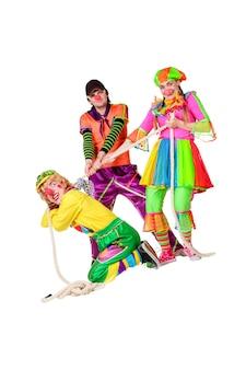Drei lächelnde clowns mit seil isoliert auf weißem hintergrund