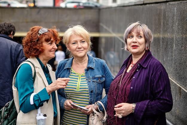 Drei lächelnde frauen mittleren alters stehen in der nähe der unterführung und unterhalten sich.
