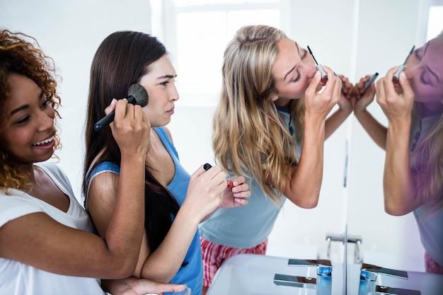 Drei lächelnde freunde, die zusammen make-up in das badezimmer einsetzen