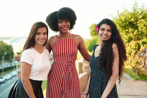 Drei lächelnde freundinnen. multiethnische gruppe von frauen, die im freien bleiben