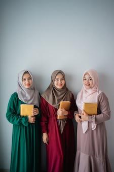 Drei lächelnde hijab-frauen halten das heilige buch al-quran