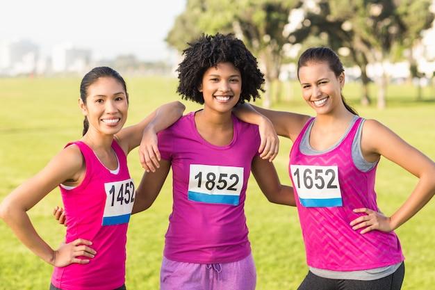 Drei lächelnde läufer, die brustkrebsmarathon stützen