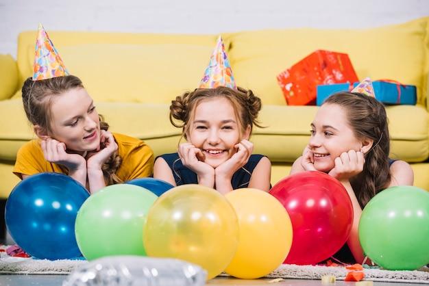 Drei lächelnde mädchen, die zu hause auf teppich mit bunten ballonen liegen