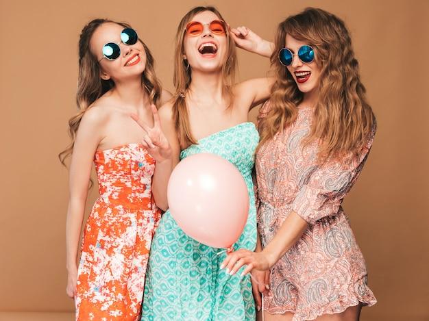 Drei lächelnde schöne frauen in den sommerkleidern. mädchen posieren. modelle mit bunten luftballons. spaß haben, bereit zum feiergeburtstag oder zur urlaubsparty