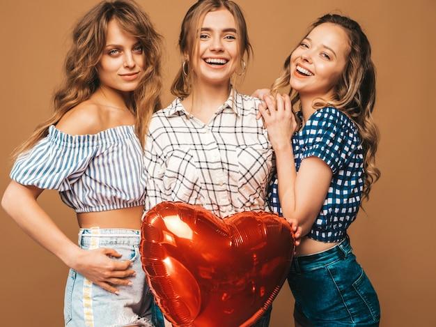 Drei lächelnde schöne sexy frauen im karierten hemdsommer kleidet. mädchen posieren. modelle mit herzformballon. bereiten sie für feier valentinstag vor