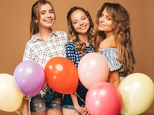 Drei lächelnde schönheiten im karierten hemdsommer kleidet. mädchen posieren. modelle mit bunten luftballons. spaß haben, bereit zum feiergeburtstag