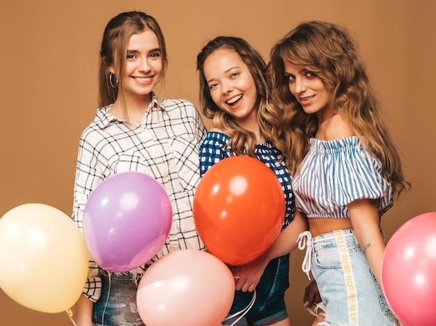 Drei lächelnde schönheiten im karierten hemdsommer kleidet. mädchen posieren. modelle mit bunten luftballons. spaß haben, bereit zur feiergeburtstagsfeier