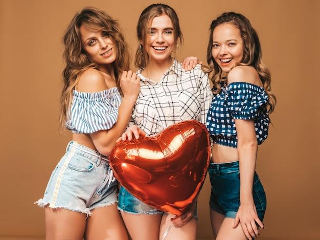 Drei lächelnde schönheiten im karierten hemdsommer kleidet. mädchen posieren. modelle mit herzformballon. bereiten sie für feier valentinstag vor