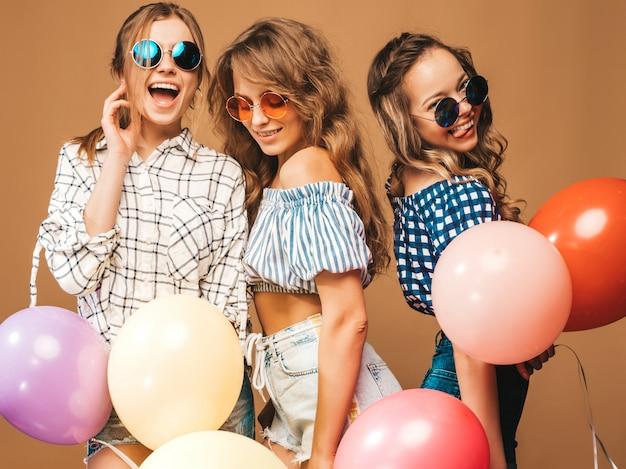 Drei lächelnde schönheiten in der karierten hemdsommerkleidung und -sonnenbrille. mädchen posieren. modelle mit bunten luftballons. spaß haben, bereit zur feiergeburtstagsfeier