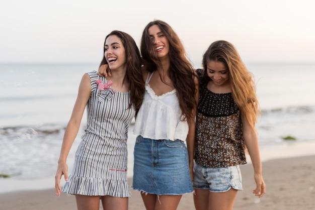 Drei lächelnde weibliche freunde am strand