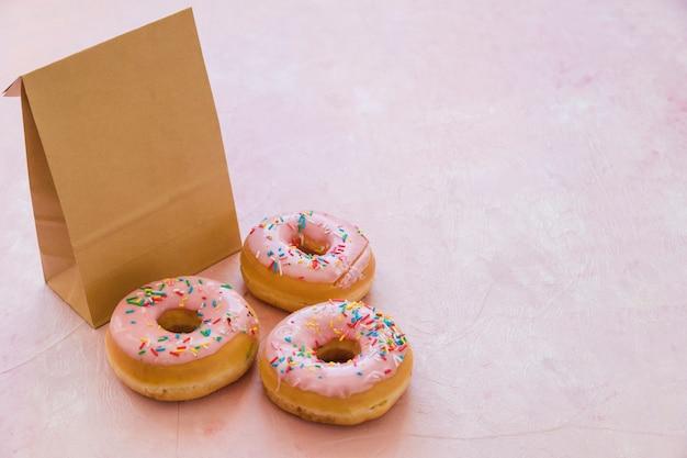 Drei leckere donuts mit paket auf rosa hintergrund
