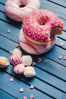Drei leckere donuts und bunte süßigkeiten