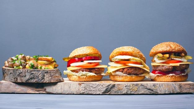 Drei leckere verschiedene hamburger mit pommes und pilzen, bestreut mit frühlingszwiebeln auf waldholzuntersetzern auf grauem hintergrund. herzhaftes mittagessen.