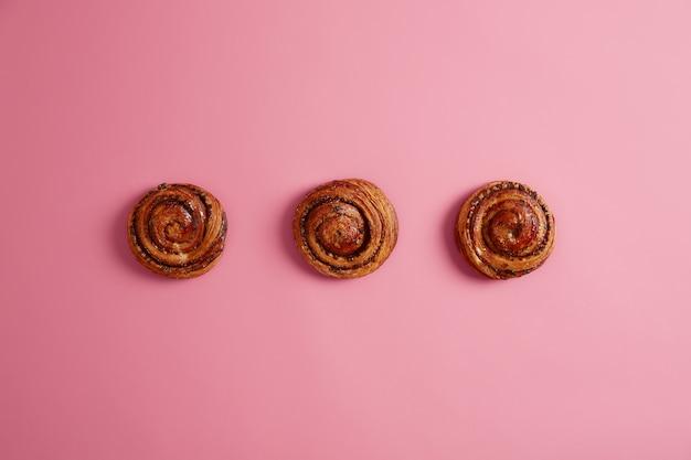 Drei leckere weiche brötchen mit aromatischem geruch, gekauft im bäckerladen, lokalisiert auf rosa hintergrund. brötchen mit zucker. bäckerei für rezeptbuch. leckeres süßes essen, desserts. oben schuss. gebackenes gebäck.