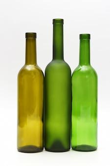 Drei leere flaschen wein auf weißem hintergrund