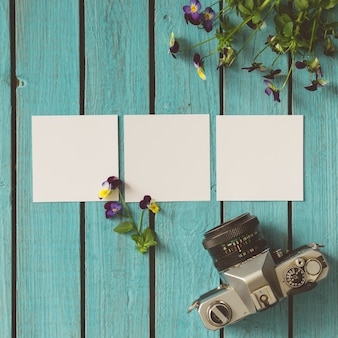Drei leere fotos auf hölzerner sommerwand mit blumen und weinlesekamera. flach liegen.
