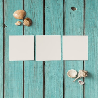 Drei leere fotos auf hölzerner sommerwand mit muscheln. flach liegen.